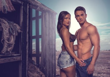 Two Sexy Couple Posing Beside Old Wooden House