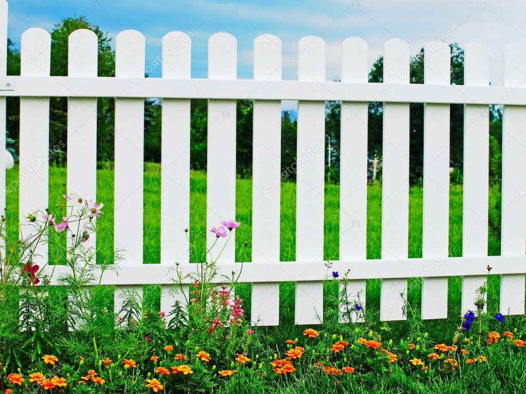 weißer zaun auf grünen rasen mit blumen — stockfoto © zurbagan #28869507