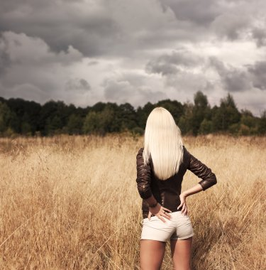 Blonde Woman Posing at the Field. Rear View