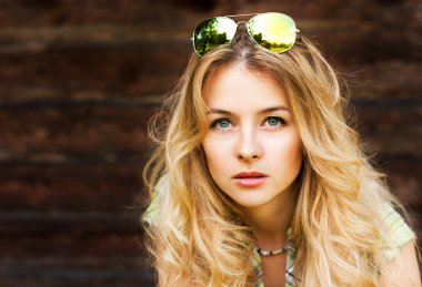 Portrait of Blonde Woman at the Wooden Wall