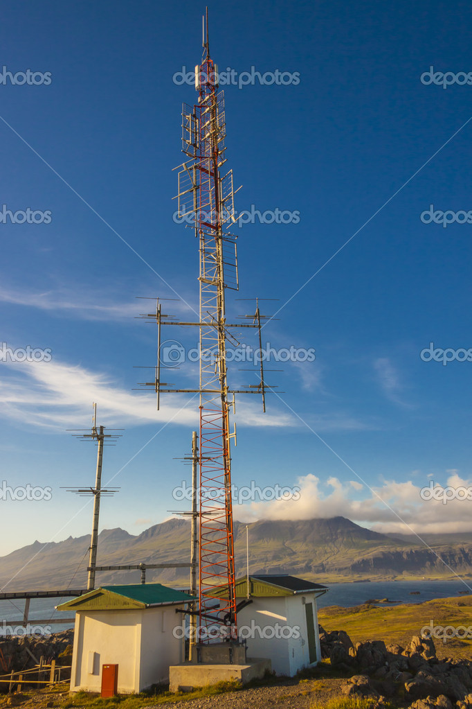 Telecommunications anetena on hill in Djupivogur village - Icela
