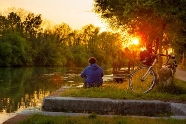 Embankment in Treviso, Italy, the guy alone relax and enjoy the sunset