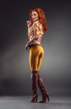 Fashion shot of sexy redhead woman in stylish outfit