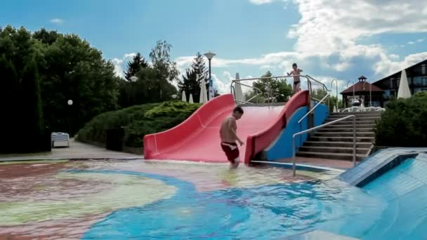 Happy boys on slide in the summer outdoor pool