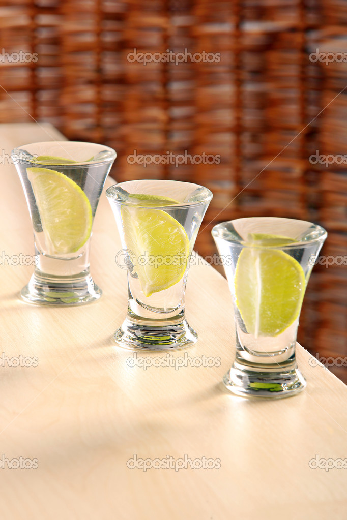 Three glasses of vodka with lime on the table — Stock Photo ...