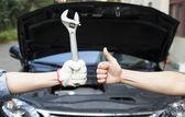 Fotografie ruka mechanik s nástroj a palec nahoru