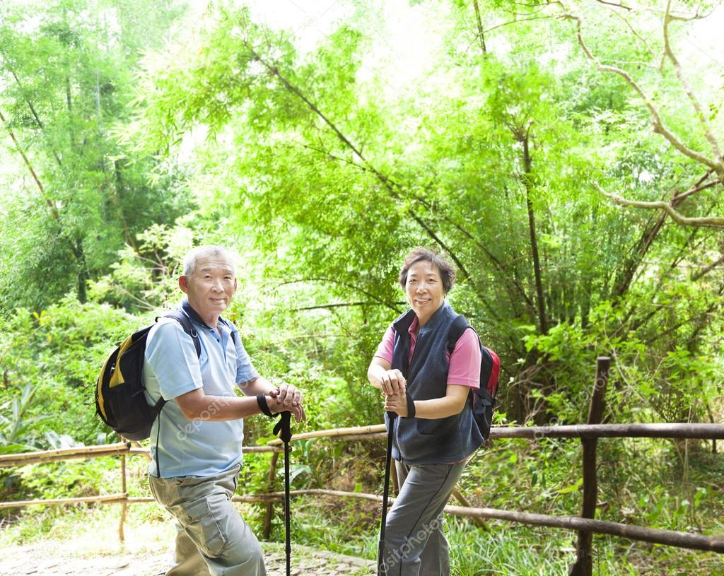 Senior couple hiking in the nature with bamboo background