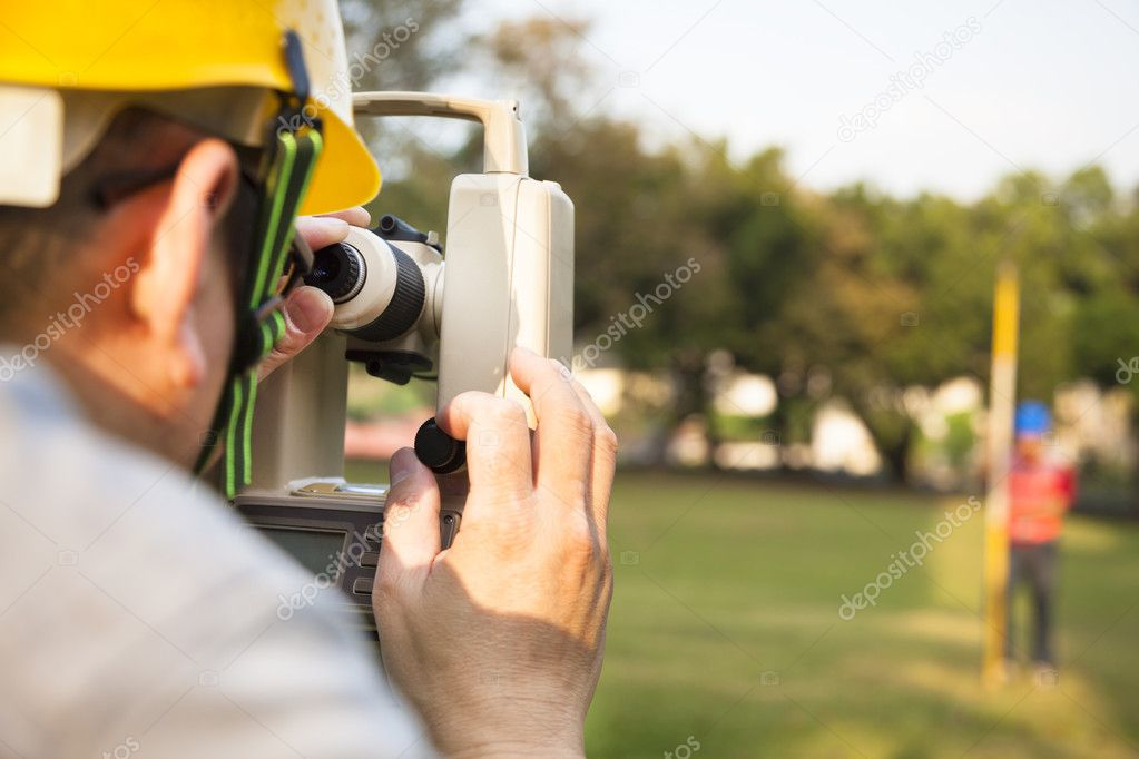 Surveyor engineer with partner making measure on the field