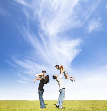 Happy family on the grass with cloud background