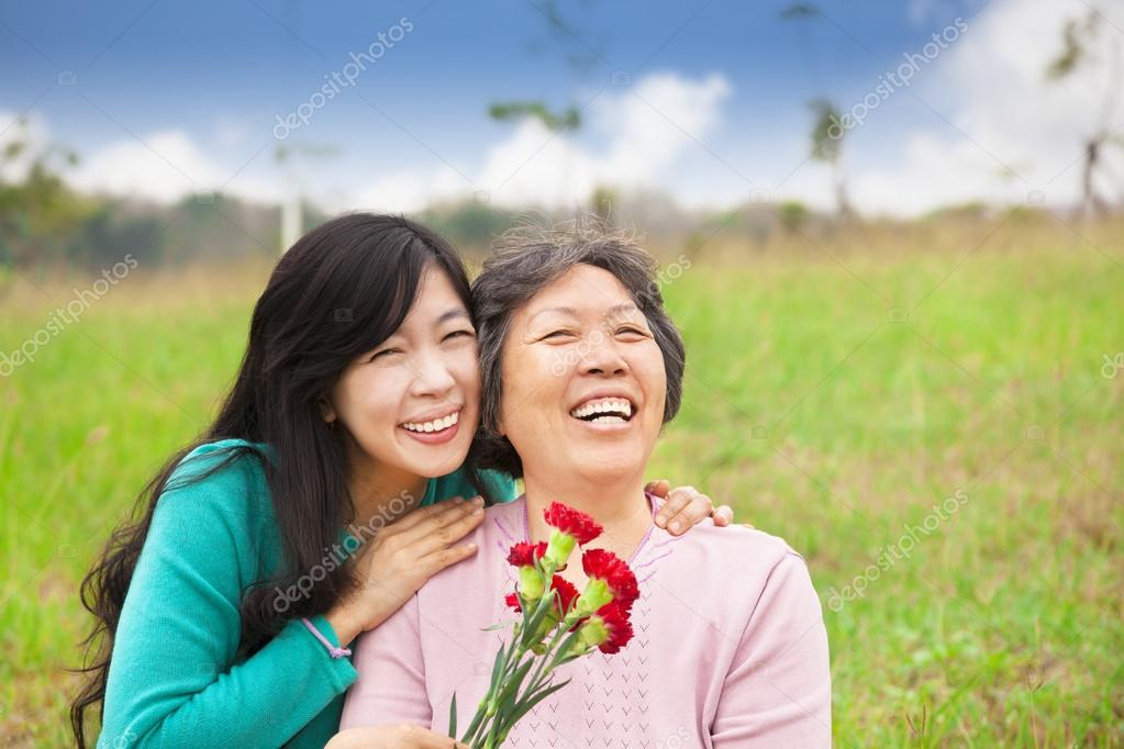 Smiling daughter and her mother with carnation flower on the gra