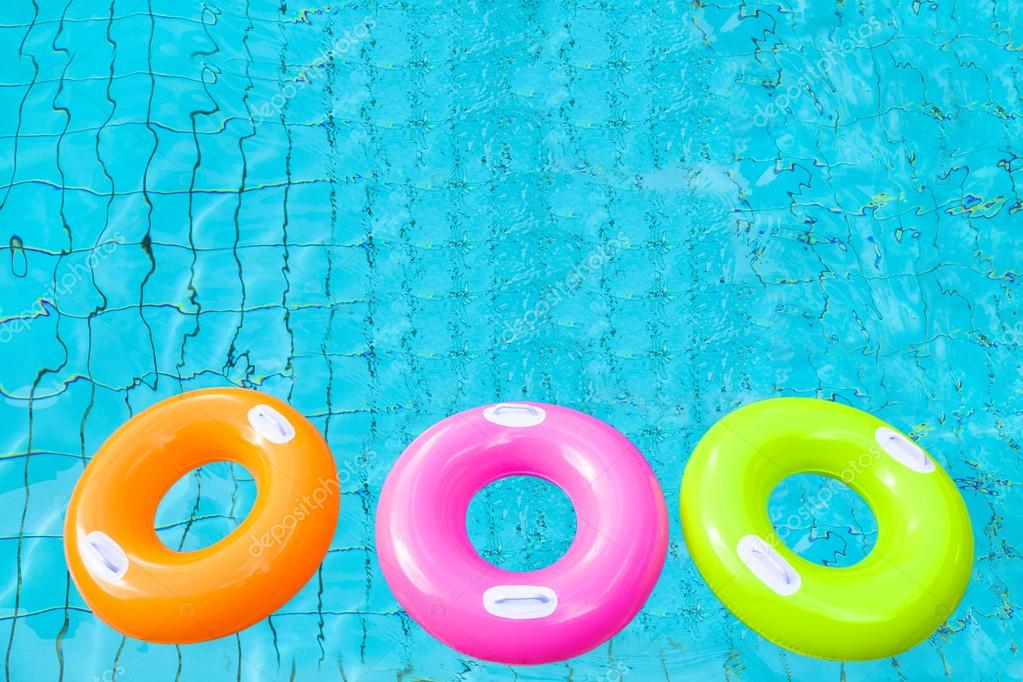 three colorful swimming pool rings on the water