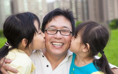 Happy little girls kissing their father