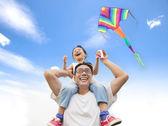 šťastná holčička na rameni otec s barevný drak
