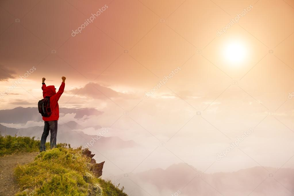 Young man with backpack standing on top of mountain watching t
