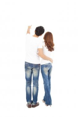 rear view of young couple looking and pointing