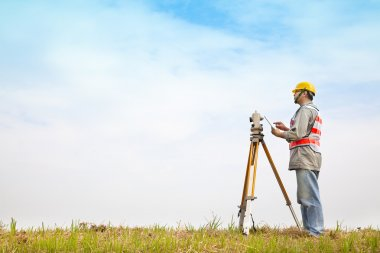 Surveyor engineer making measure on the field with tablet pc