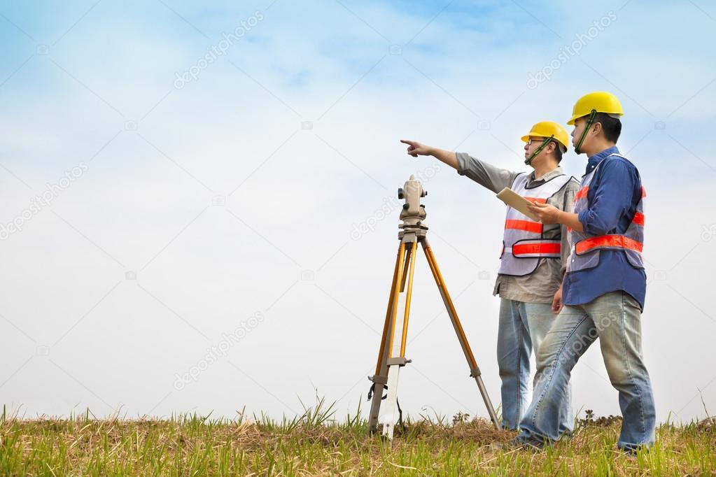 Surveyor engineer making measure with partner on the field