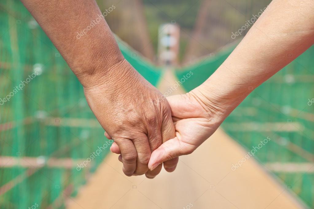 senior homme avec couple femme tenant par la main marchant sur le bridg photographie tomwang. Black Bedroom Furniture Sets. Home Design Ideas