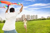 šťastná rodina hraje barevné draka v městském parku