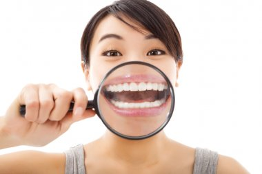 funny girl holding magnifying to tooth