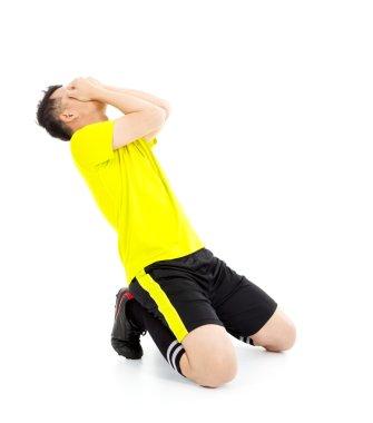 Upset  or excited soccer player kneeling down