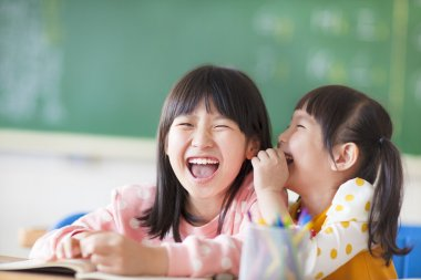 Laughing little girls sharing secrets in class