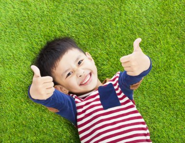 Smiling kid lying and thumb up  on a meadow