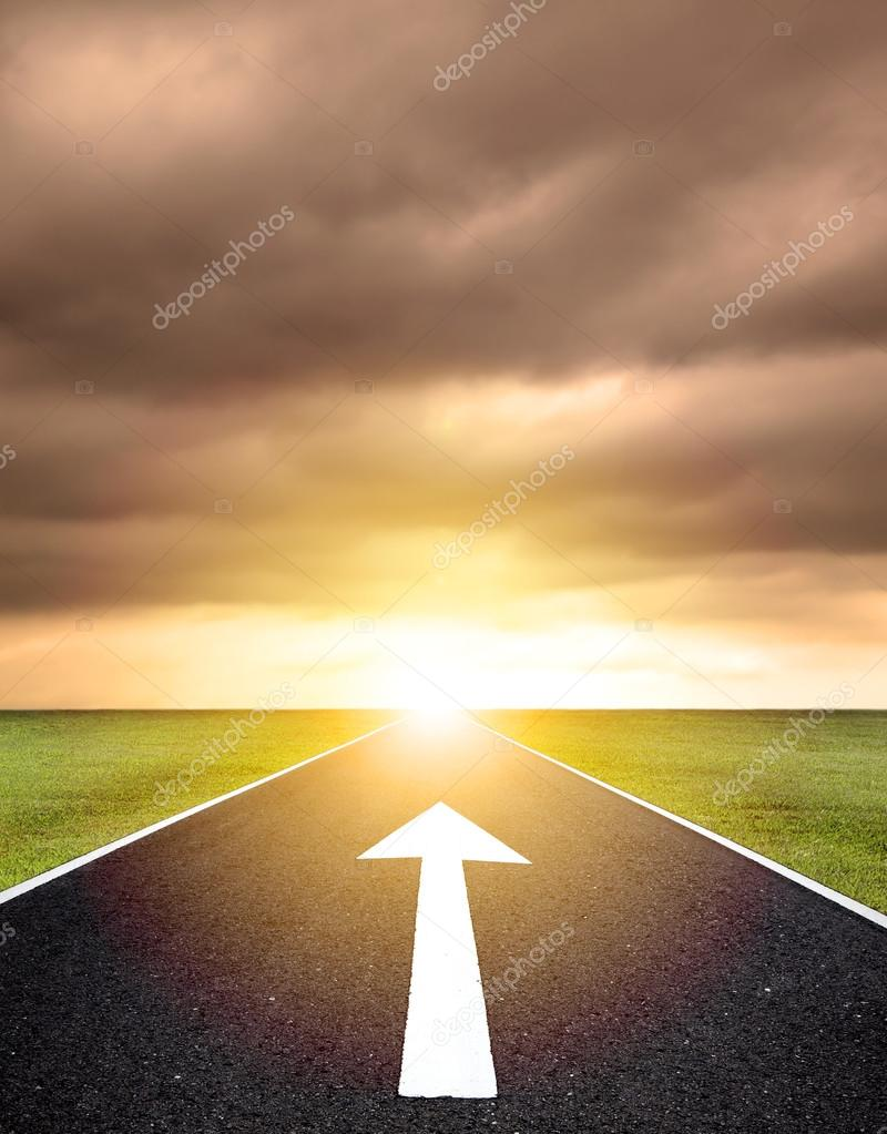 the ahead arrow on the asphalt road  and sunset background