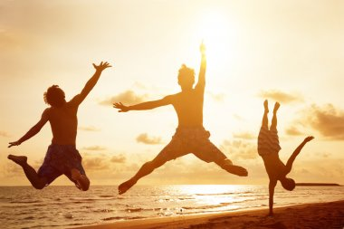 young people jumping on the beach with sunset background
