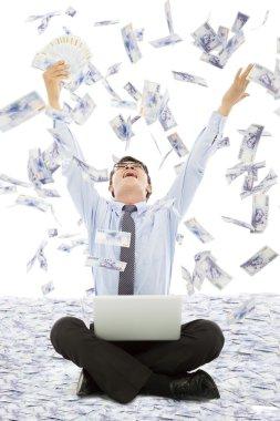 Business man winning a lottery with money rain background