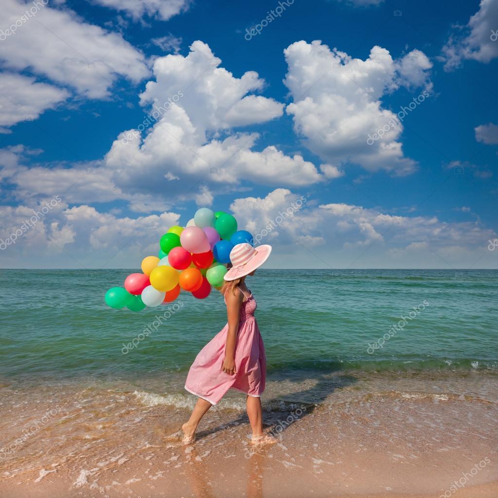 Giovane donna che cammina sulla spiaggia con palloncini - Immagine con palloncini ...
