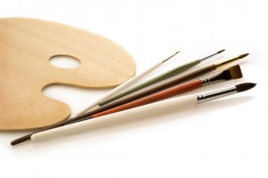 Brushes with wooden palette on white