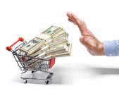 Podnikatel je ruka  nákupní vozík plný stohy dolarových bankovek - izolované na bílém pozadí