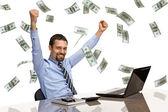 A kezével, miközben dolgozik a laptop-val eső pénzt emelt üzletember