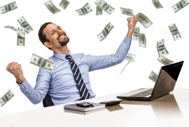 Young modern businessman excited with his success while working with his laptop computer with money rain