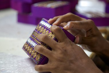 Close-up of hands working on a purple box in India