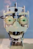 Hlava robota s legrační zelenýma očima a legrační výraz