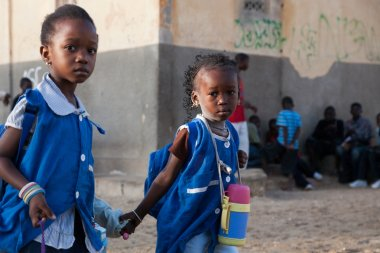 African girls dressed in blue on the way to school in Senegal