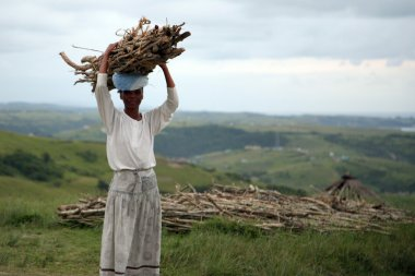 African woman resting while carrying wood in South Africa