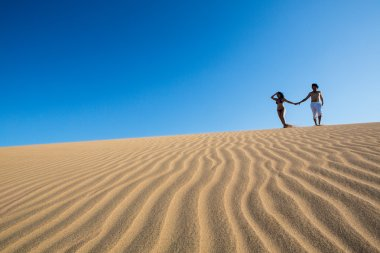 Beautiful and happy young couple walking in the sand