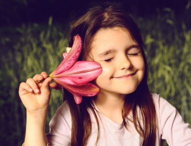 Girl put your ear flower, listen to the sounds of nature