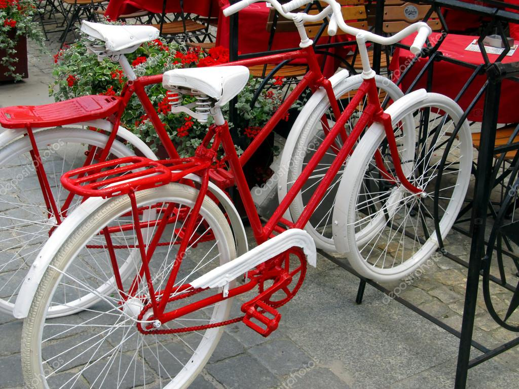 Two bikes for women and men, painted white and red standing in a rack