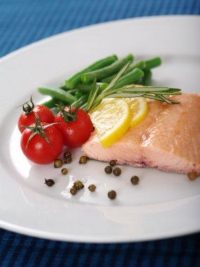 Photo of a cooked salmon steak with rosemary, lemon slices, cherry tomatoes, green beans, and peppercorns on a white plate. stock vector