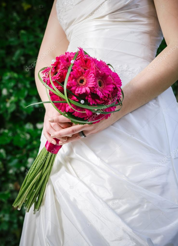 Photo of a bride in a white dress holding flowers.