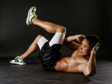 Asian man exercising his stomach muscles
