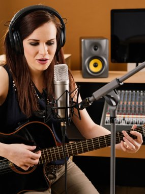 Photo of a beautiful brunette in a recording studio playing an acoustic guitar and singing into a large diaphragm microphone. stock vector