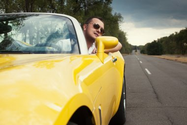 Trendy guy in sunglasses driving yellow convertible car. Bad weather