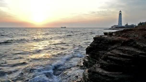 západ slunce na skalnaté pobřeží, maják na pozadí