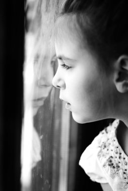 Little girl looking through window with reflections