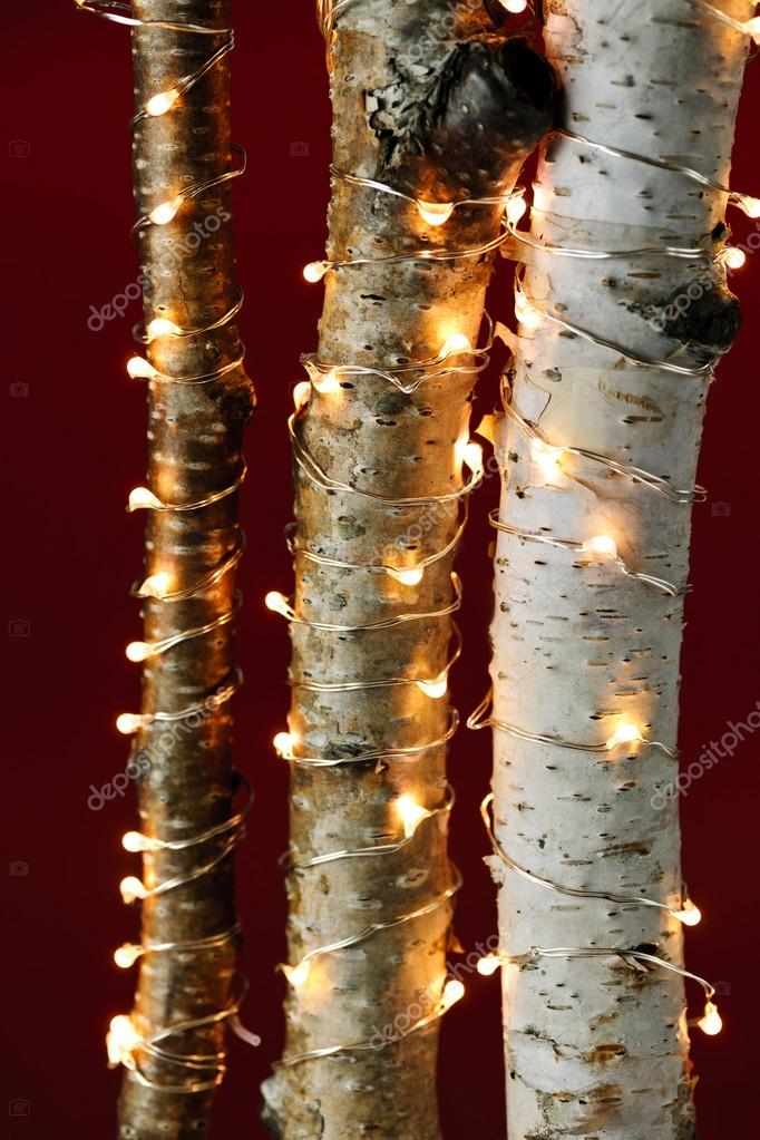 birch trees wrapped in christmas lights on red background photo by elenathewise